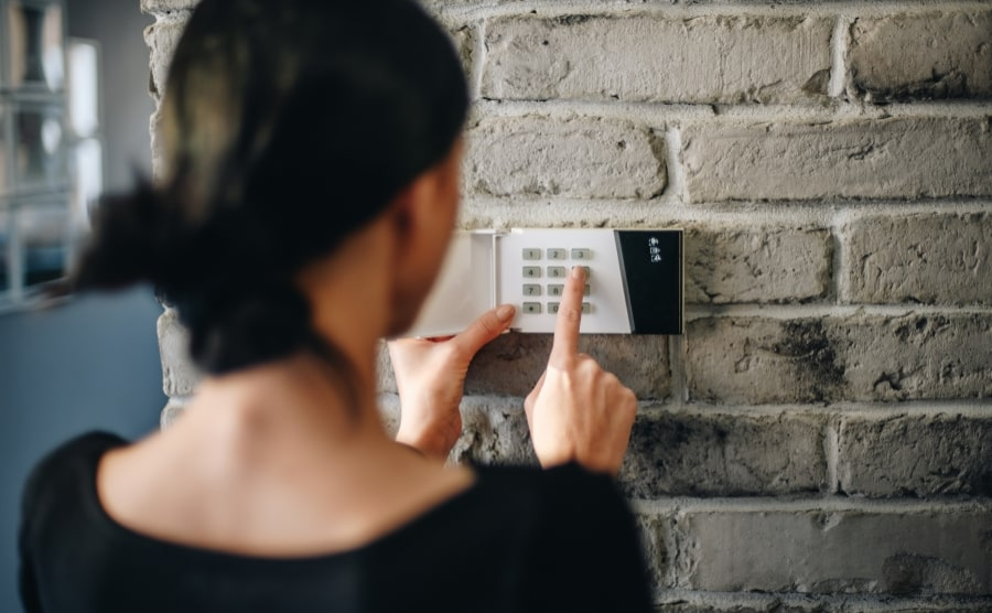 Woman setting home security system