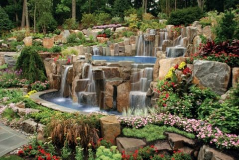 backyard waterfalls with colorful plants