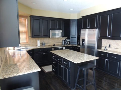 Black cabinetry with marble surface