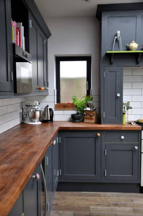Black cabinetry with wooden surface